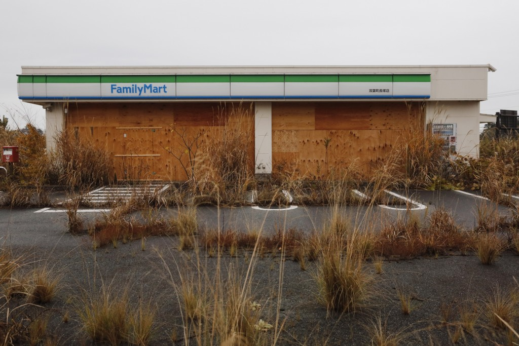 Weeds grow in the parking lot of a deserted convenient store Wednesday, Nov. 27, 2019, in the abandoned town of Futaba, Fukushima prefecture, Japan. H...