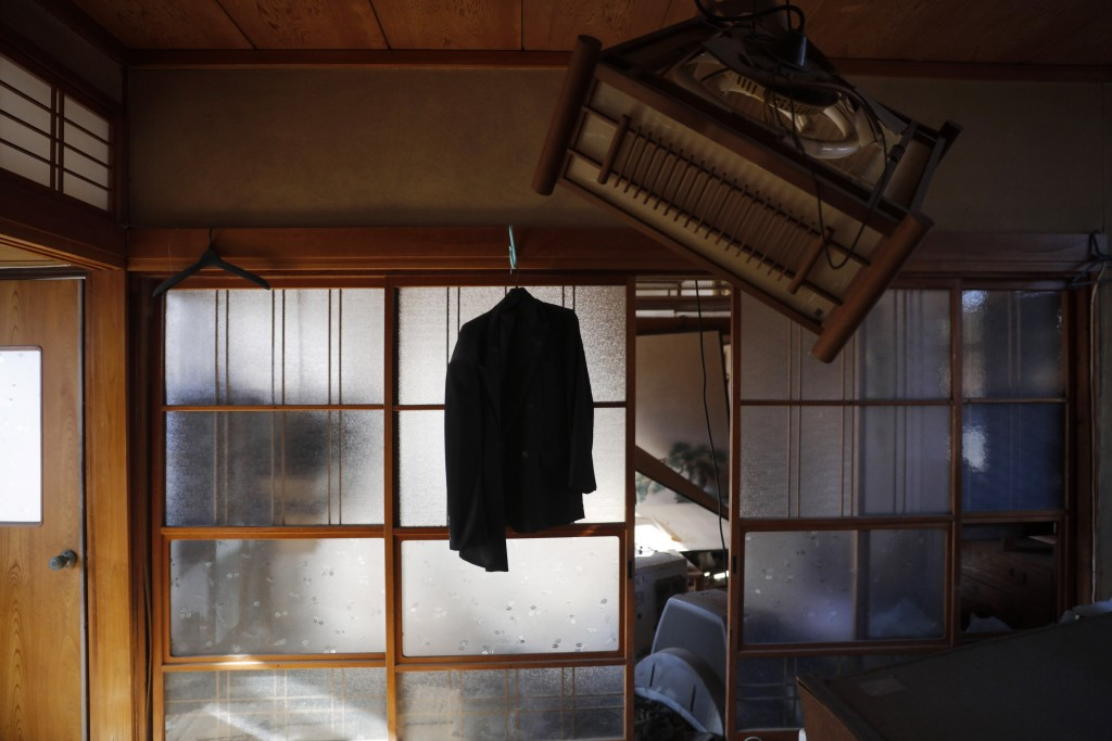 A jacket hangs on a hanger in an abandoned home Tuesday, Dec. 3, 2019, in Futaba, Fukushima prefecture, Japan. The entire town was evacuated after the...