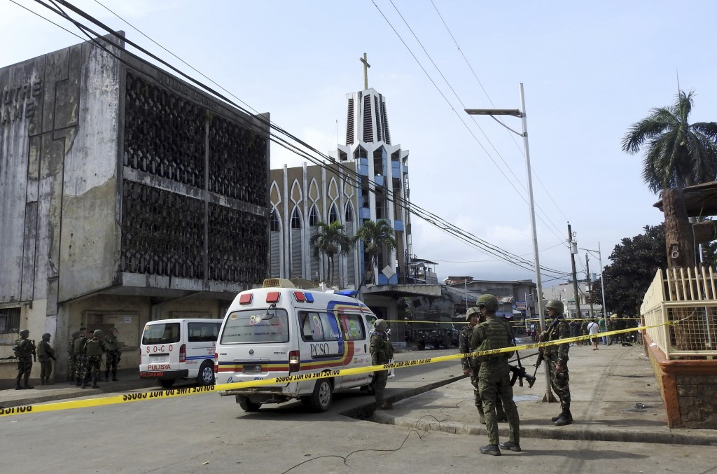 FILE - In this Jan. 27, 2019, file photo, police investigators and soldiers attend the scene after two bombs exploded outside a Roman Catholic cathedr...
