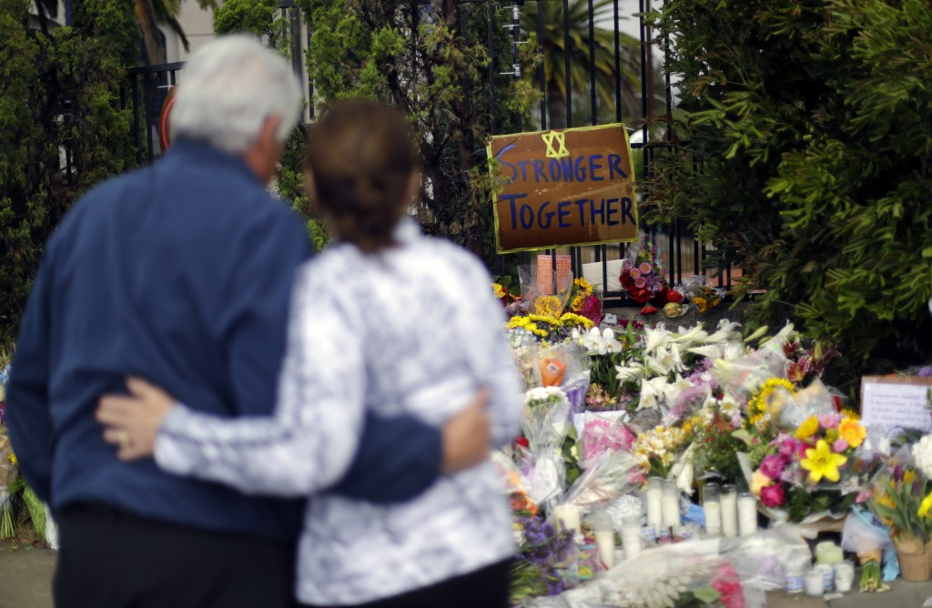 FILE - In this April 29, 2019, file photo, a couple embrace near a growing memorial across the street from the Chabad of Poway synagogue in Poway, Cal...