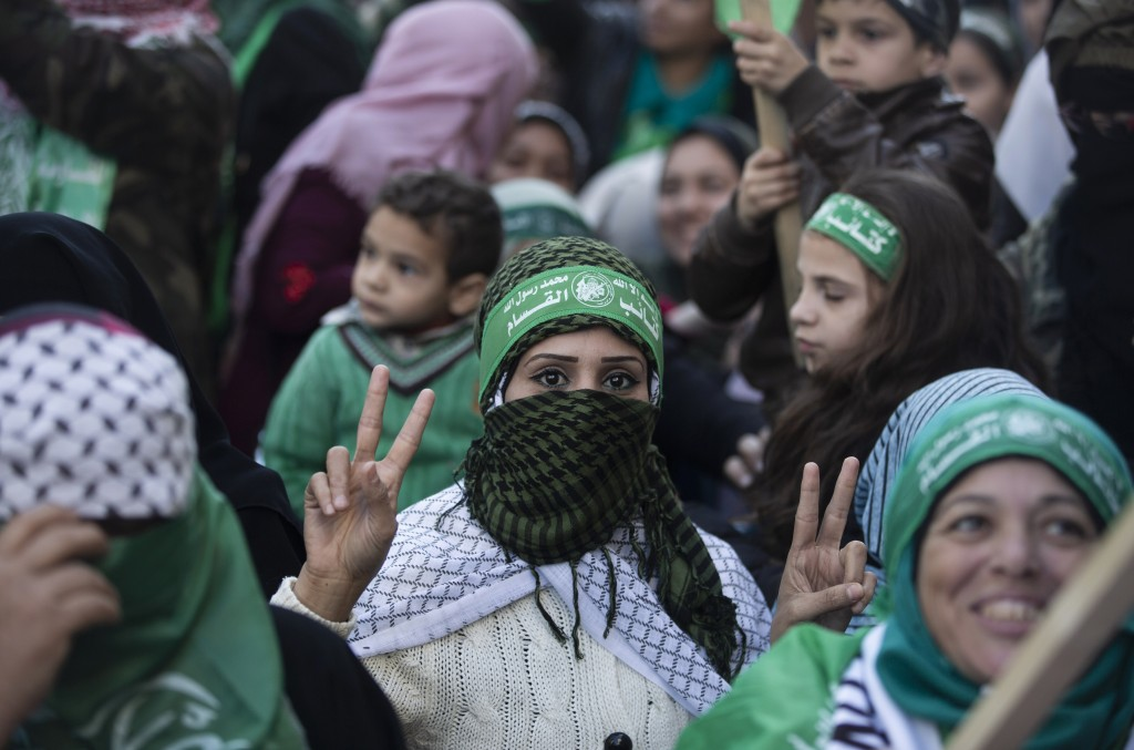 """A Palestinian woman flashes the victory sign and wears a headband with Arabic that reads: """"No God but Allah and Muhammed is his messenger, al-Qassam B..."""