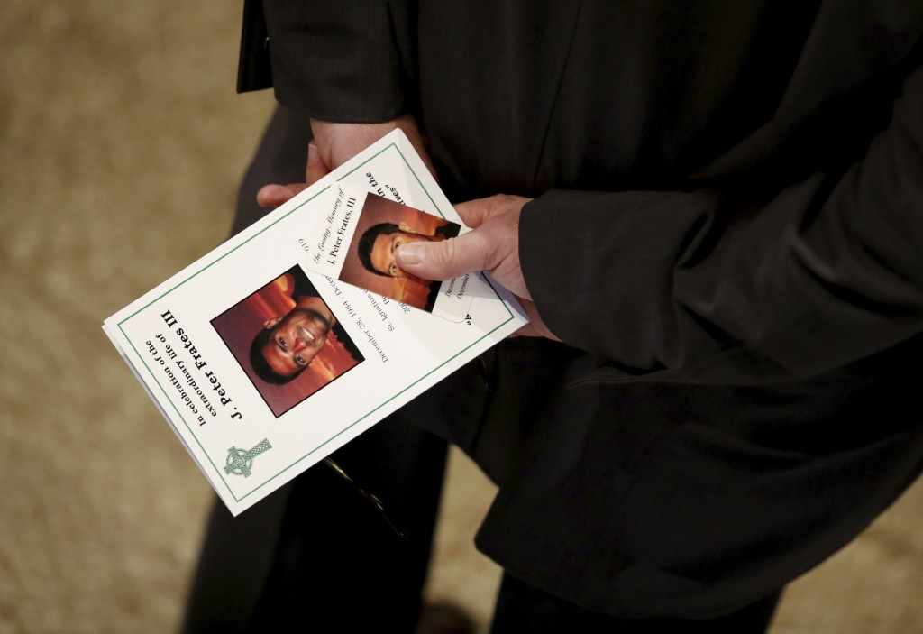 A man carries a program during a funeral mass for Pete Frates at St. Ignatius of Loyola Parish church at Boston College in Boston, Friday, Dec. 13, 20...