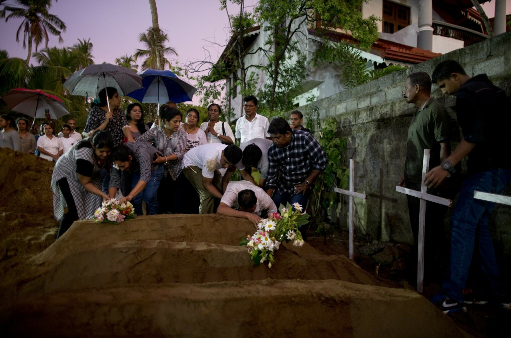 FILE - In this April 22, 2019, file photo, relatives place flowers after the burial of three victims of the same family, who died in an Easter Sunday ...