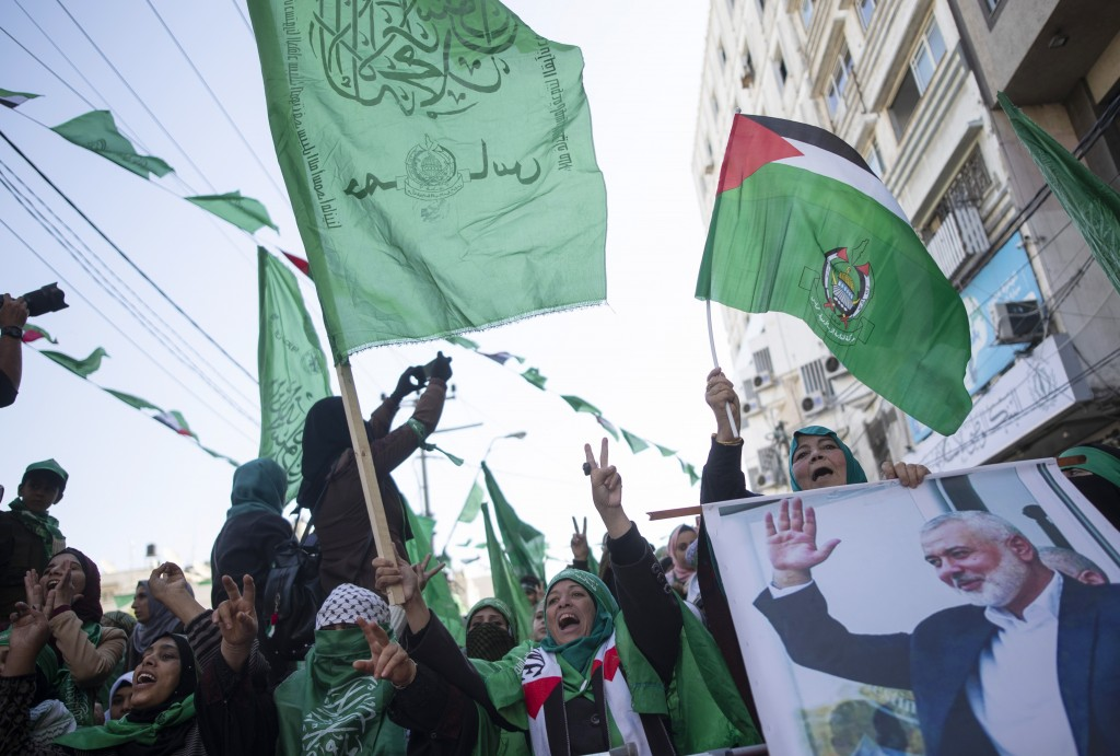 Palestinian women, one holding a picture of Hamas movement chief, Ismail Haniyeh, attend a mass rally marking the 32nd anniversary of the founding of ...