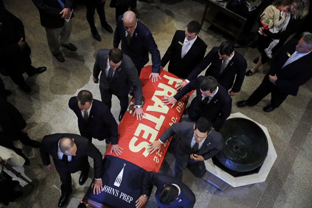 Pallbearers escort the casket of Pete Frates, draped in a flag bearing his name, following a funeral mass at St. Ignatius of Loyola Parish church at B...
