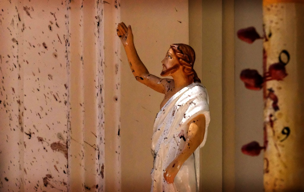 FILE - In this April 21, 2019, file photo, bloodstains a Jesus Christ statue at the St. Sebastian's Church after a blast in Negombo, north of Colombo,...