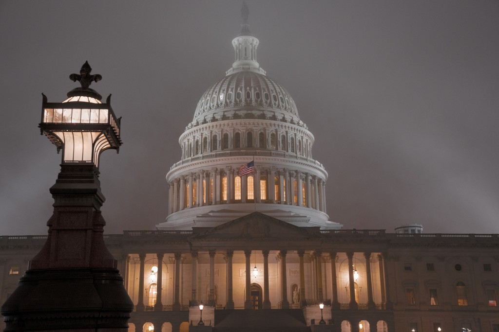 The U.S. Capitol in Washington is shrouded in mist, Friday night, Dec. 13, 2019.  This coming week's virtually certain House impeachment of President ...