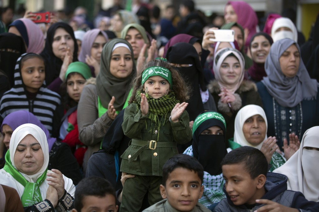 """A Palestinian girl, center, wears a headband with Arabic that reads: """"No God but Allah and Muhammed is his messenger, al-Qassam Brigades"""" during a mas..."""