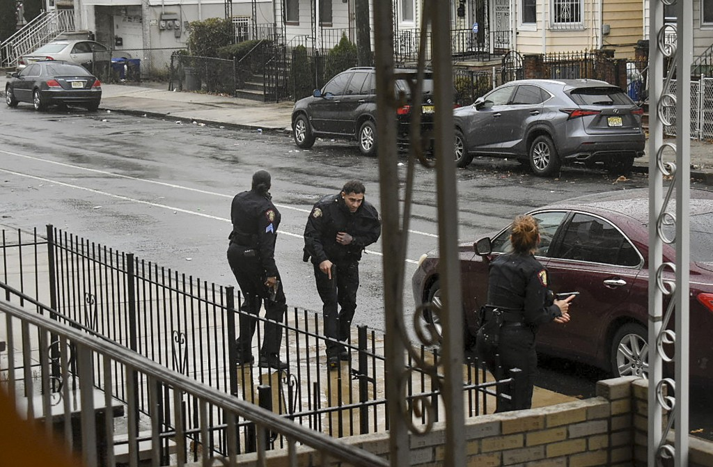 In this Dec. 10, 2019 photo, Jersey City police Sgt. Marjorie Jordan, left, helps fellow officer Raymond Sanchez to safety after he was shot during a ...