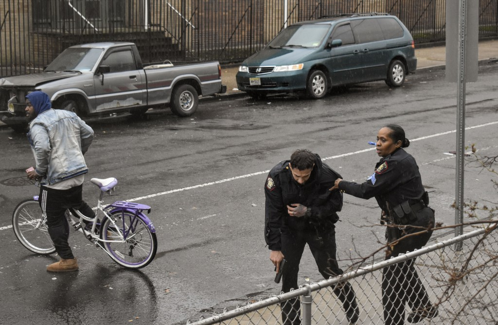 In this Dec. 10, 2019 photo, Jersey City police Sgt. Marjorie Jordan, right, helps fellow officer Raymond Sanchez to safety after he was shot during a...
