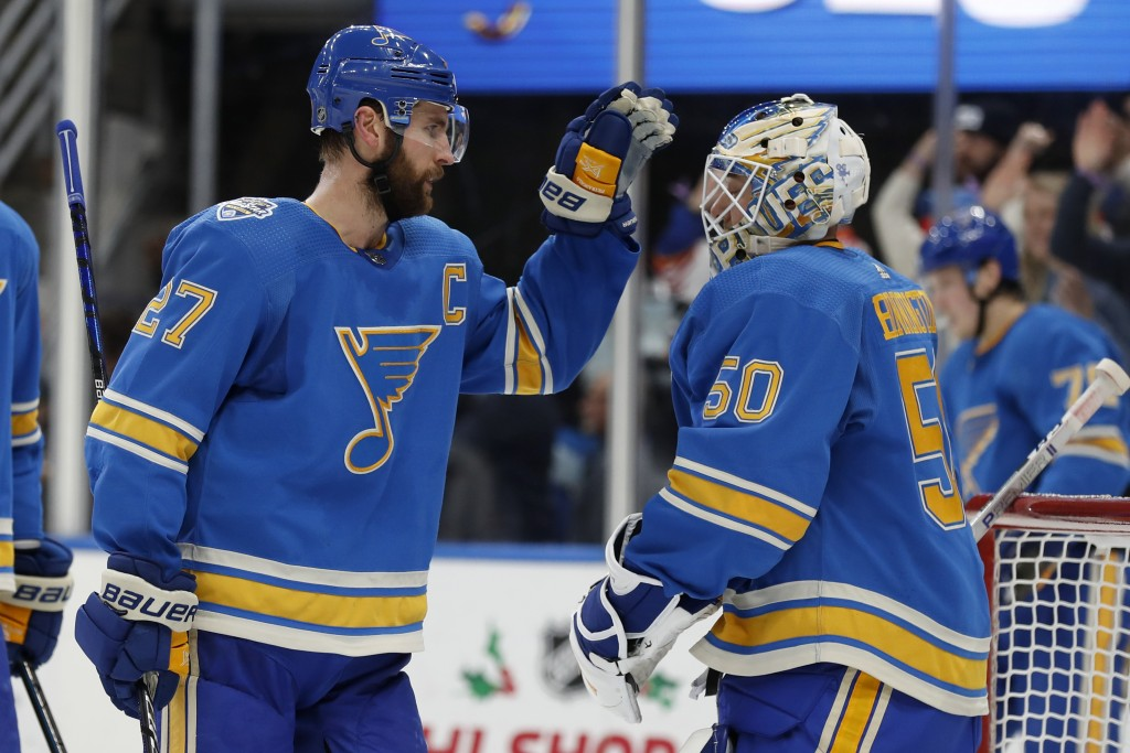 St. Louis Blues' Alex Pietrangelo, left, and goaltender Jordan Binnington celebrate a 4-3 victory over the Chicago Blackhawks in an NHL hockey game Sa...