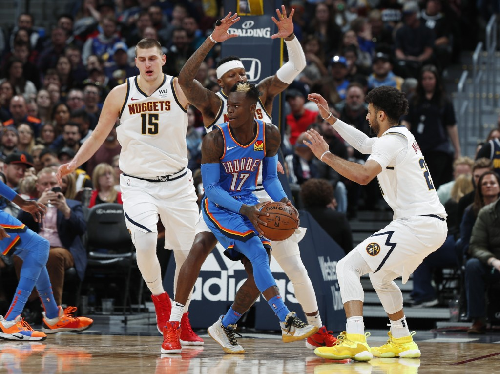 Oklahoma City Thunder guard Dennis Schroder, front, is surrounded while trying to pass the ball by, from back left, Denver Nuggets center Nikola Jokic...
