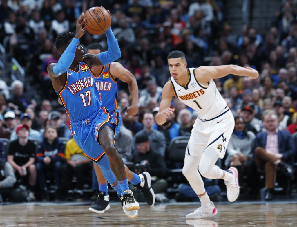 Oklahoma City Thunder guard Dennis Schroder, left, pulls in a loose ball as Denver Nuggets forward Michael Porter Jr. pursues in the first half of an ...