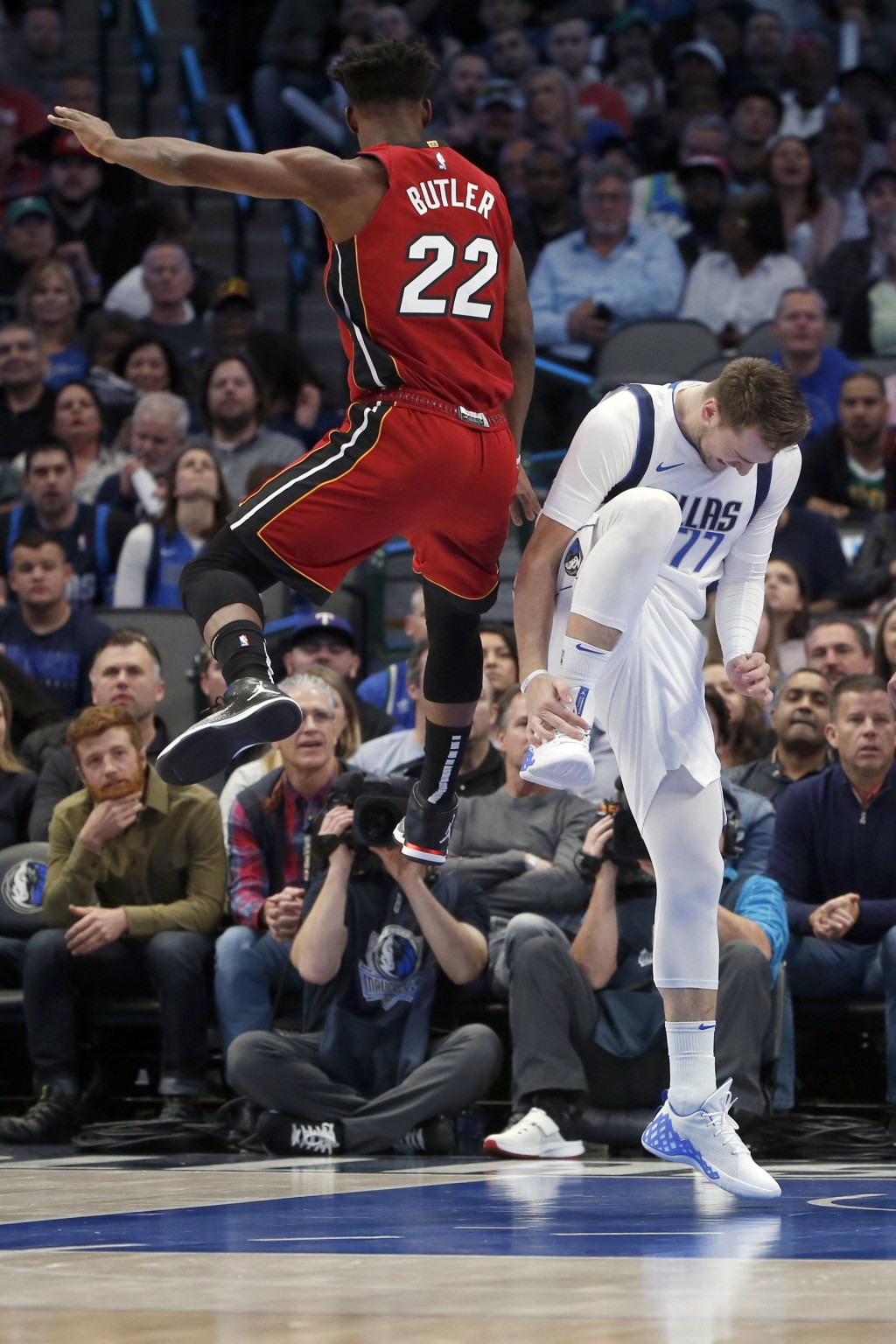 Dallas Mavericks forward Luka Doncic (77) reacts after injuring his ankle as Miami Heat forward Jimmy Butler (22) defends him during the first half of...