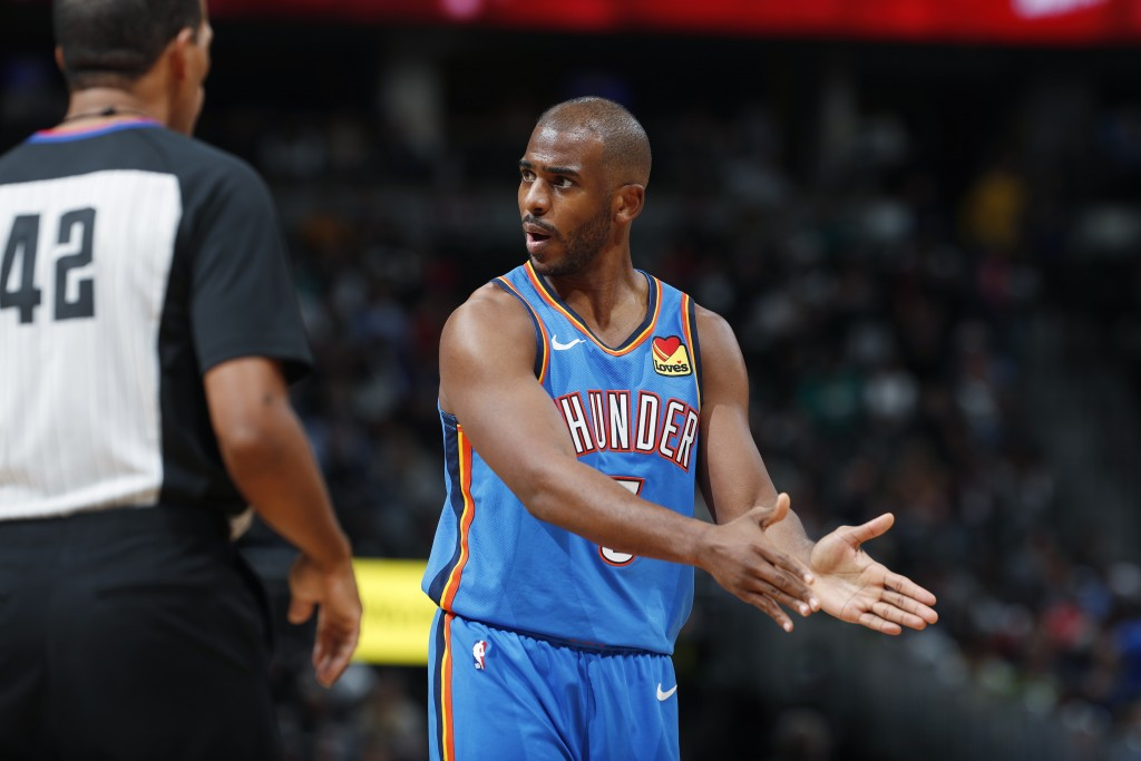 Oklahoma City Thunder guard Chris Paul, right, argues for a call with referee Eric Lewis in the second half of an NBA basketball game against the Denv...