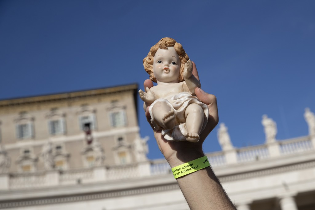 A child holds up a statue of baby Jesus as Pope Francis blesses them during the Angelus noon prayer he celebrated from the window of his studio overlo...