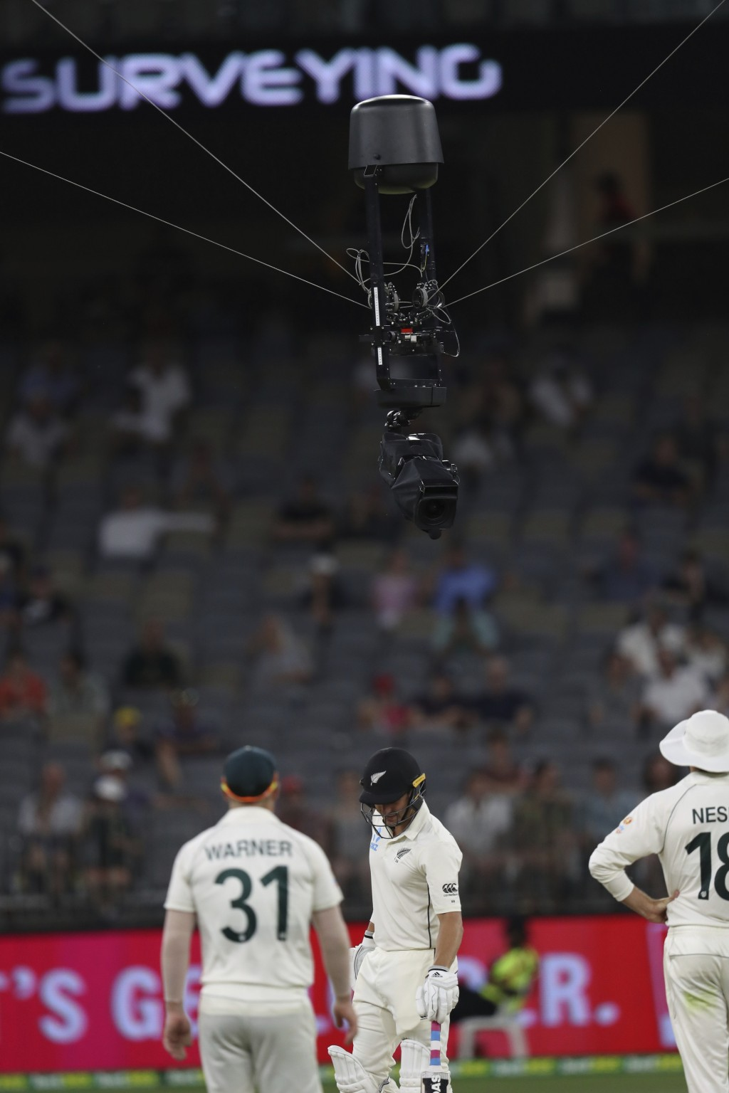 Players look at a cable suspended Television camera that got stuck over the pitch, holding up play during the cricket test between Australia and New Z...