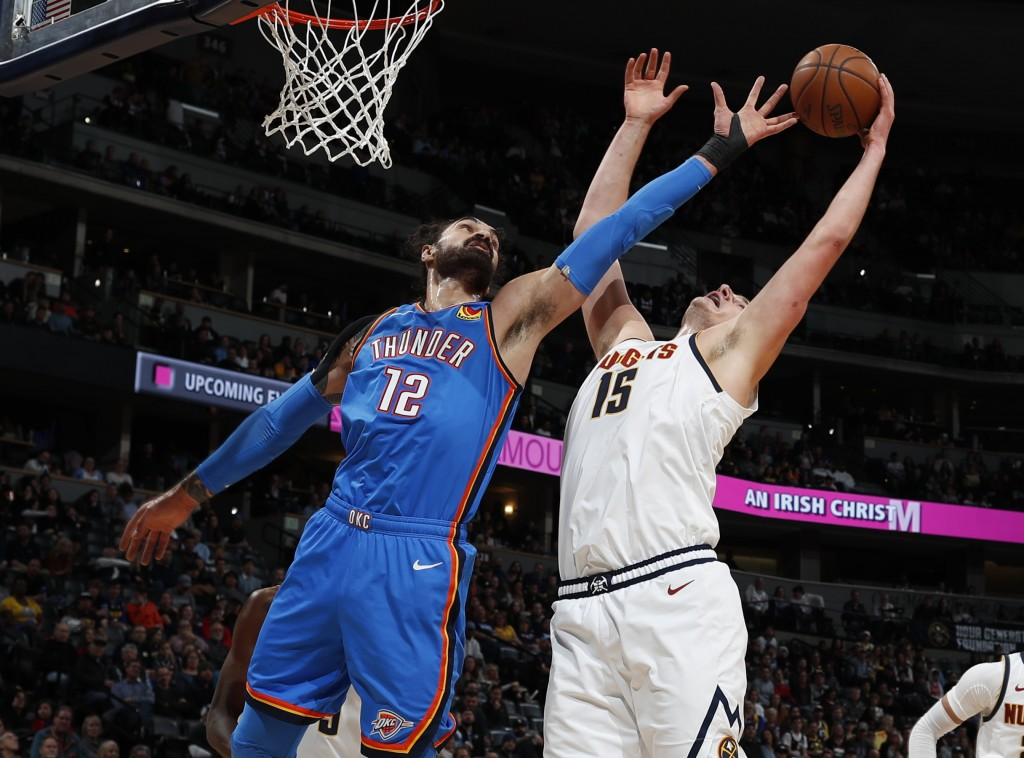 Oklahoma City Thunder center Steven Adams , left, fights for a rebound with Denver Nuggets center Nikola Jokic in the first half of an NBA basketball ...