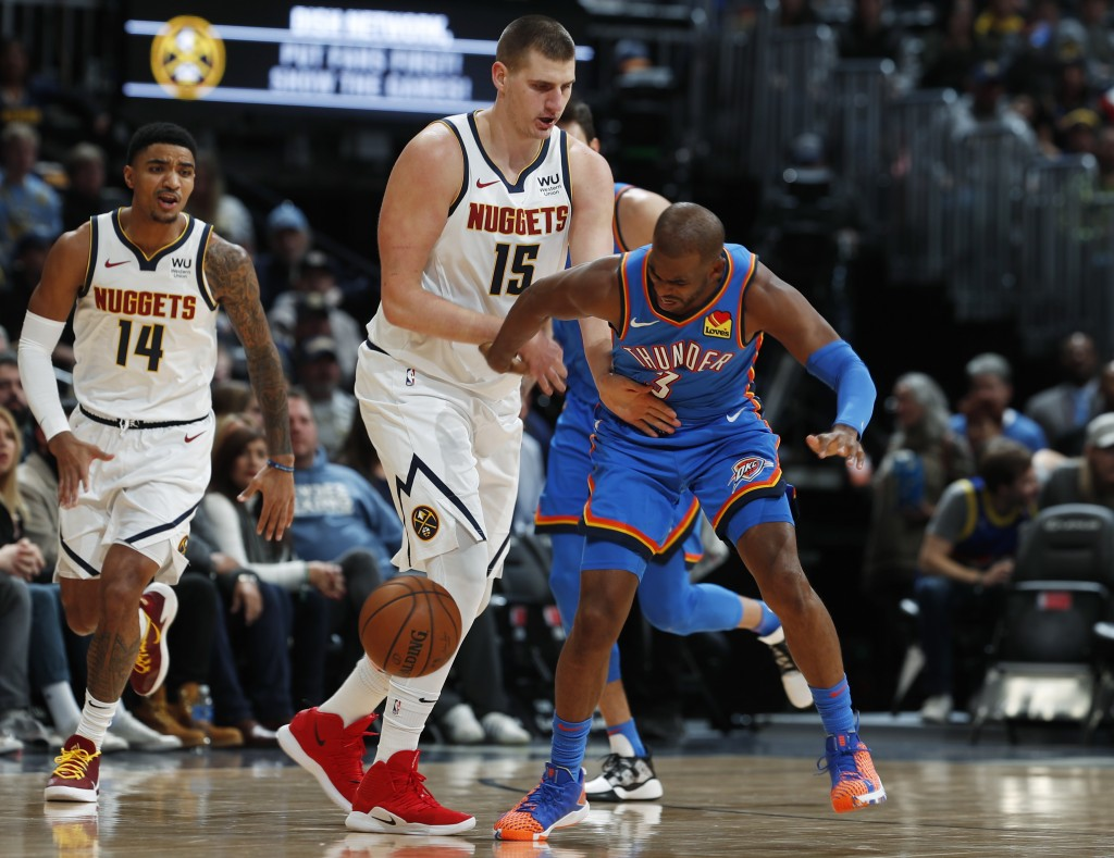 Denver Nuggets center Nikola Jokic, left, fouls Oklahoma City Thunder guard Chris Paul as he picks up a loose ball in the first half of an NBA basketb...
