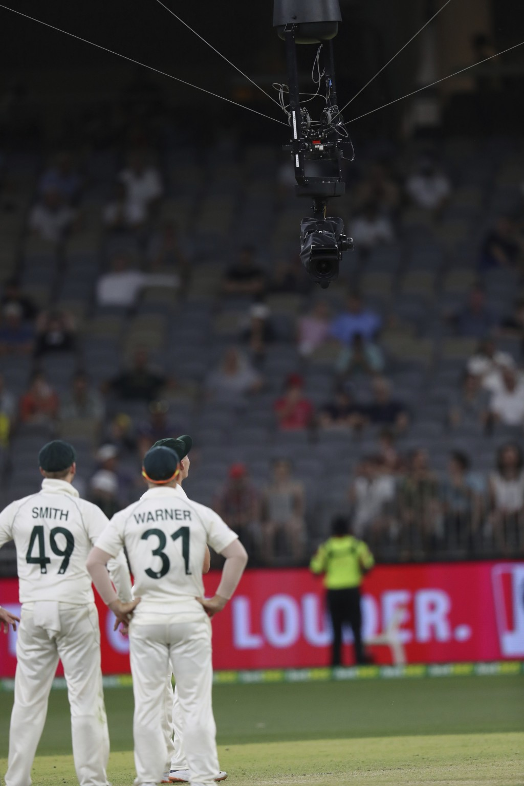 Australian players look at a cable suspended Television camera that got stuck over the pitch, holding up play during their cricket test against New Ze...