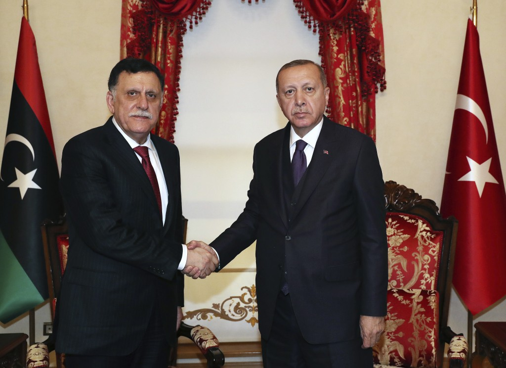 Turkey's President Recep Tayyip Erdogan, right, shakes hands with Fayez al Sarraj, the head of Libya's internationally recognised government, prior to...