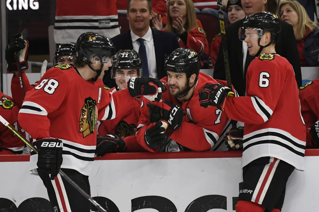 Chicago Blackhawks' Patrick Kane (88) celebrates with teammate Brent Seabrook (7) on the bench after scoring a goal during the first period of an NHL ...