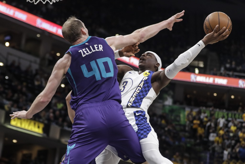 Indiana Pacers' Aaron Holiday (3) shoots against sCharlotte Hornets' Cody Zeller (40) during the second half of an NBA basketball game, Sunday, Dec. 1...