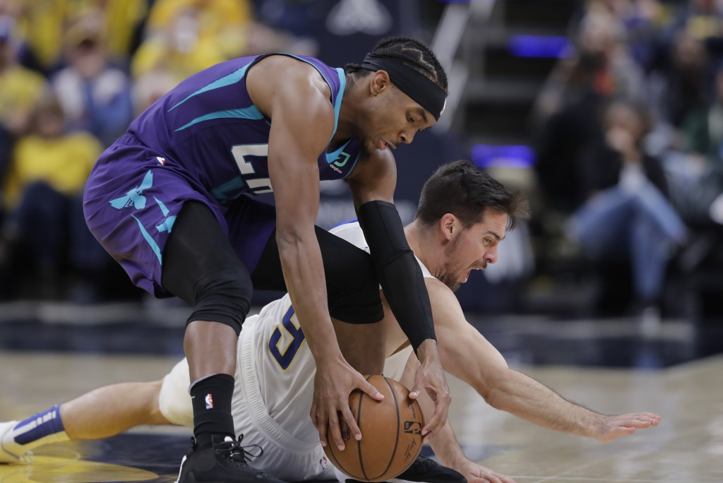 Charlotte Hornets' Devonte' Graham (4) recovers the ball against Indiana Pacers' T.J. McConnell (9) during the second half of an NBA basketball game, ...