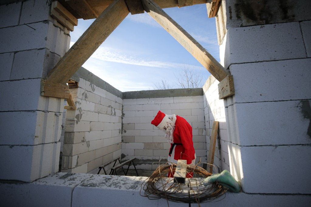 A charity worker wearing a Santa Claus costume walks after delivering Christmas presents to a poor family on the outskirts of Brasov, Romania, Sunday,...