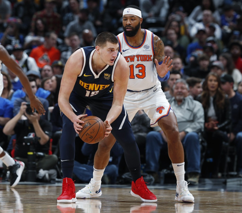 Denver Nuggets center Nikola Jokic, left, looks to pass the ball as New York Knicks forward Marcus Morris Sr. defends in the first half of an NBA bask...