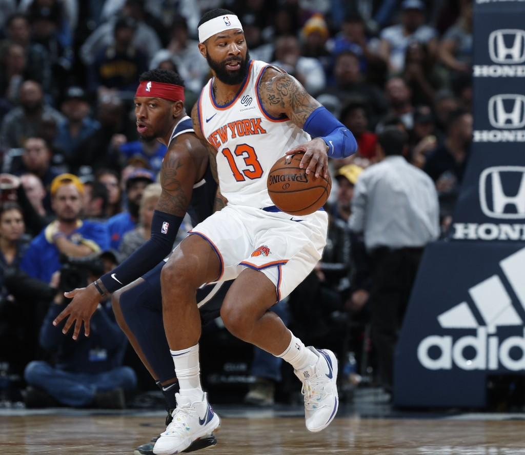 New York Knicks forward Marcus Morris Sr., front, picks up the ball as Denver Nuggets forward Torrey Craig defends in the second half of an NBA basket...