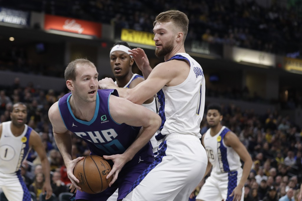 Charlotte Hornets' Cody Zeller (40) makes a pass against Indiana Pacers' Domantas Sabonis (11) during the first half of an NBA basketball game, Sunday...