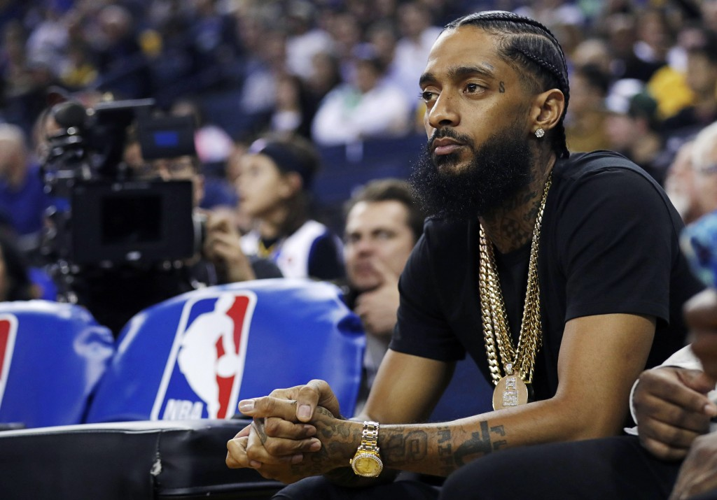 FILE - In this March 29, 2018, file photo, rapper Nipsey Hussle watches an NBA basketball game between the Golden State Warriors and the Milwaukee Buc...