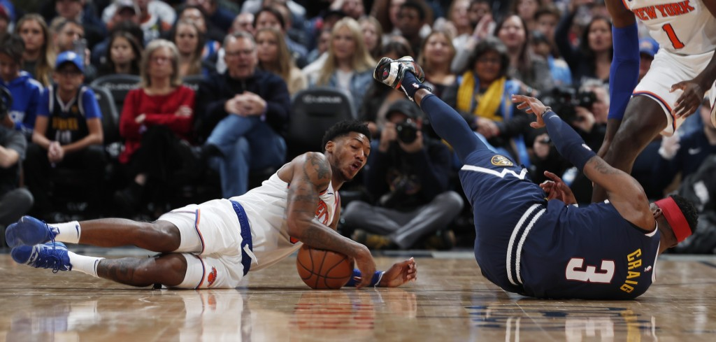 New York Knicks guard Elfrid Payton, left, recovers a loose ball as Denver Nuggets forward Torrey Craig falls on the court in the second half of an NB...