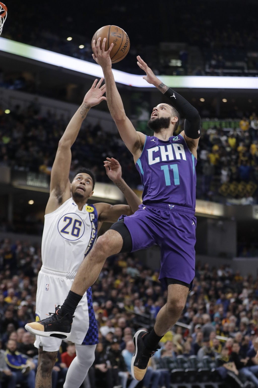 Charlotte Hornets' Cody Martin (11) shoots against Indiana Pacers' Jeremy Lamb (26) during the first half of an NBA basketball game, Sunday, Dec. 15, ...