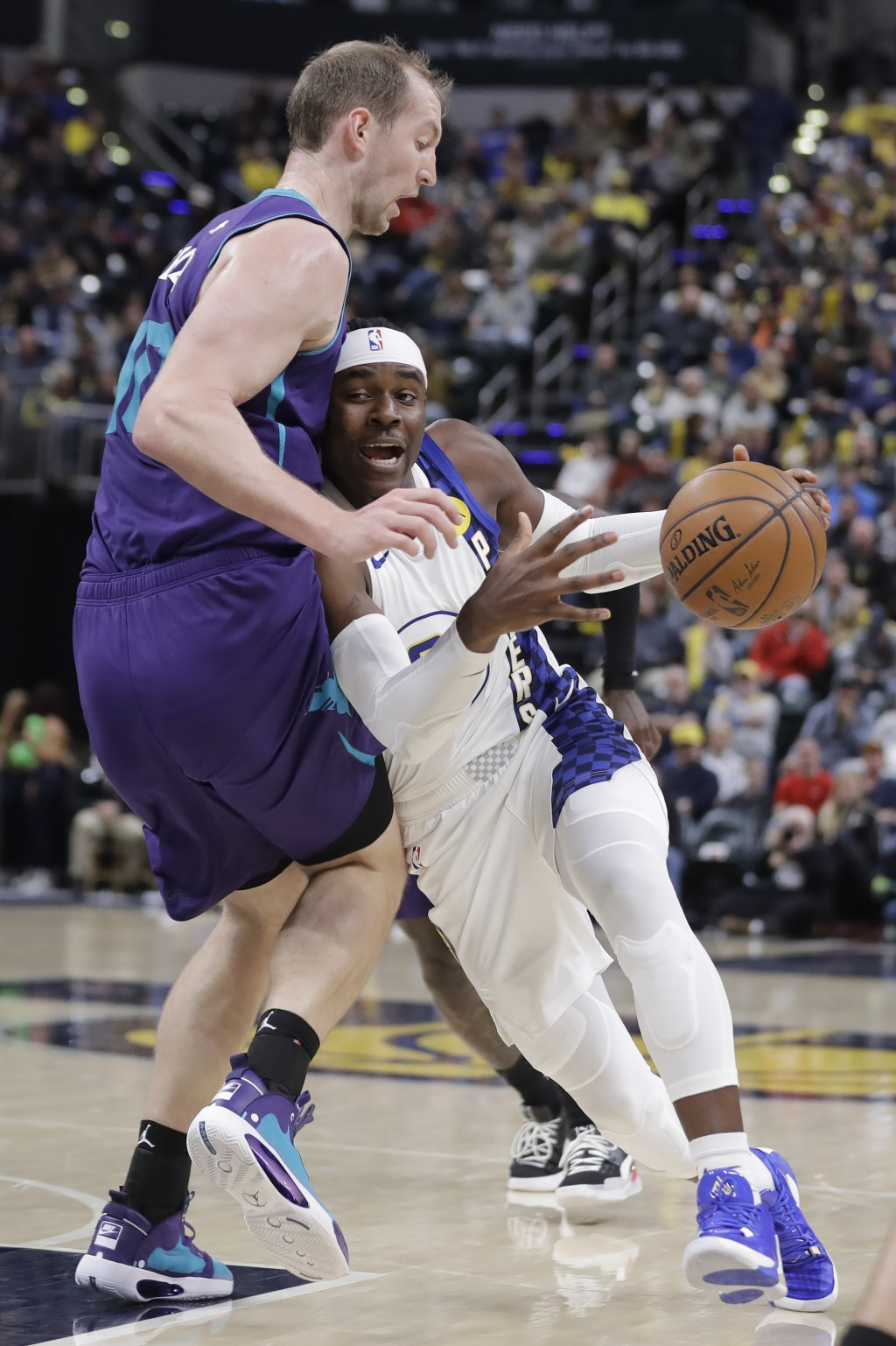 Indiana Pacers' Aaron Holiday, right, drives to the basket against Charlotte Hornets' Cody Zeller, left, during the second half of an NBA basketball g...