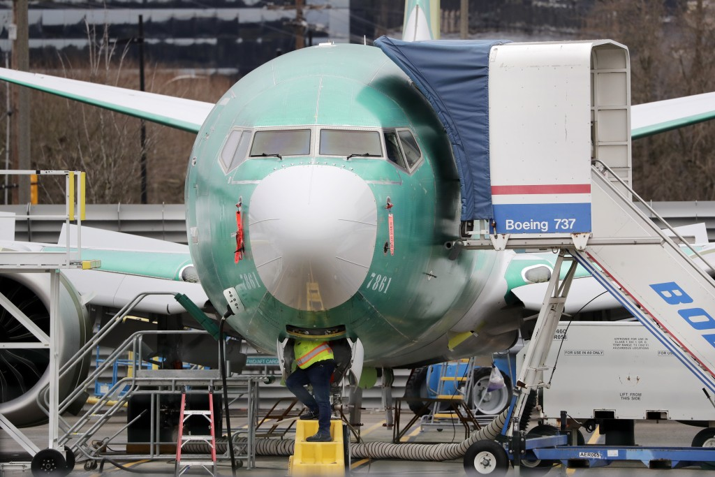 A worker looks up underneath a Boeing 737 MAX jet Monday, Dec. 16, 2019, in Renton, Wash. Shares of Boeing fell before the opening bell on a report th...