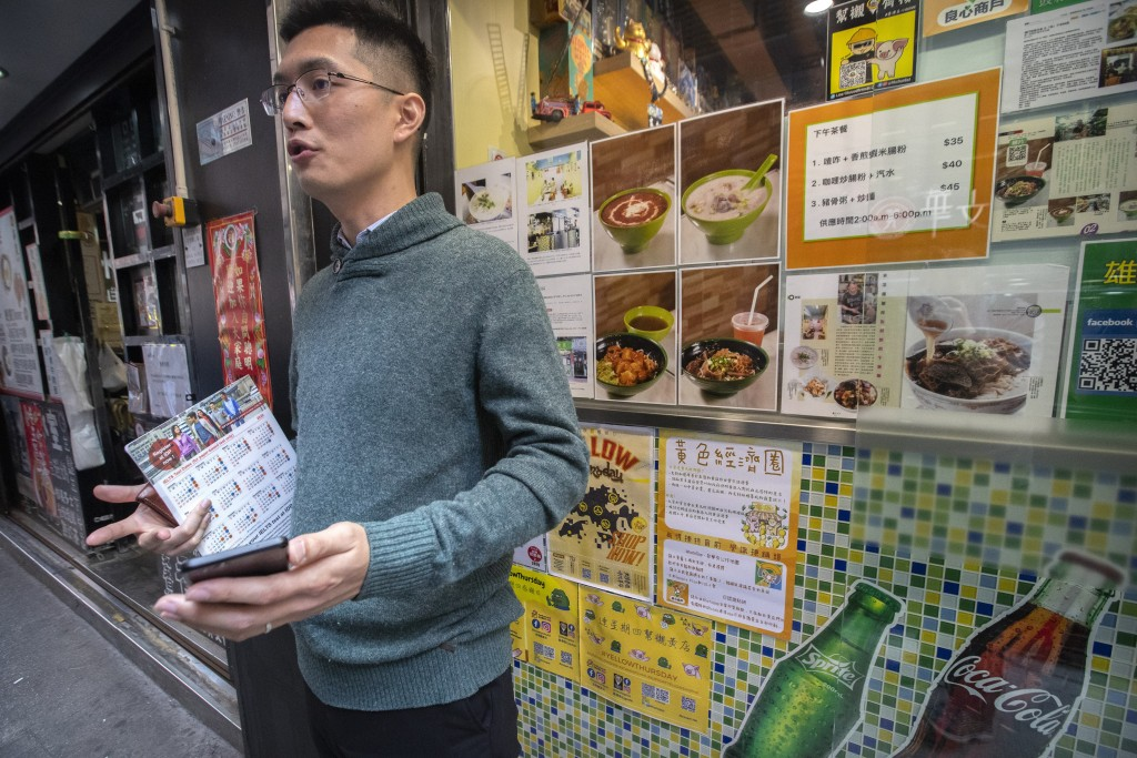 In this Dec. 13, 2019, photo, Raymond Lau talks about using smartphone apps to help guide his shopping toward protest-friendly businesses as he stands...