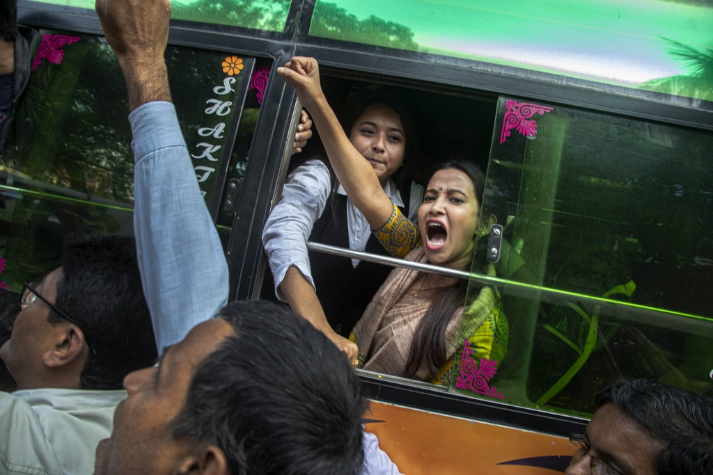 A woman shouts slogans from inside a bus after being detained during a protest against the Citizenship Amendment Act in Gauhati, India, Tuesday, Dec. ...