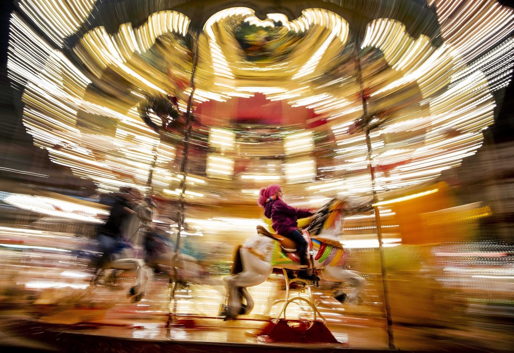 A girl rides a horse on a merry-go-round on the Christmas market in Frankfurt, Germany, Monday, Dec. 16, 2019. (AP Photo/Michael Probst)