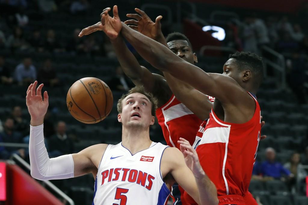 Detroit Pistons guard Luke Kennard (5) drives on Washington Wizards guard Isaac Bonga (17) and center Ian Mahinmi (28) in the first half of an NBA bas...