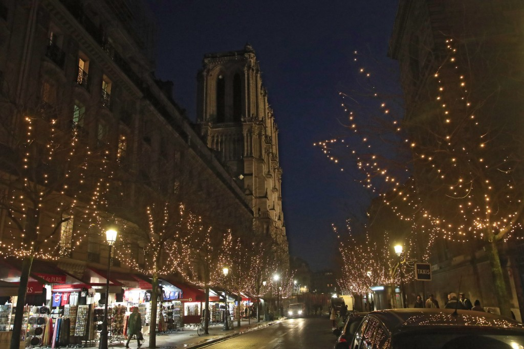 A shopper street decorated with Christmas lights leading to the Notre Dame Cathedral in Paris, Monday, Dec. 16, 2019. Notre Dame Cathedral has been ne...