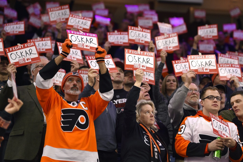 Fans hold signs in support of Philadelphia Flyers' Oskar Lindblom during a stoppage in the first period of an NHL hockey game against the Anaheim Duck...