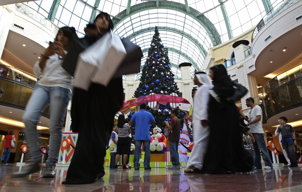 FILE- in This Wednesday, Dec. 23, 2009 file photo, Emirati couple and the other nationalities pass by a giant Christmas tree at a shopping mall in Dub...