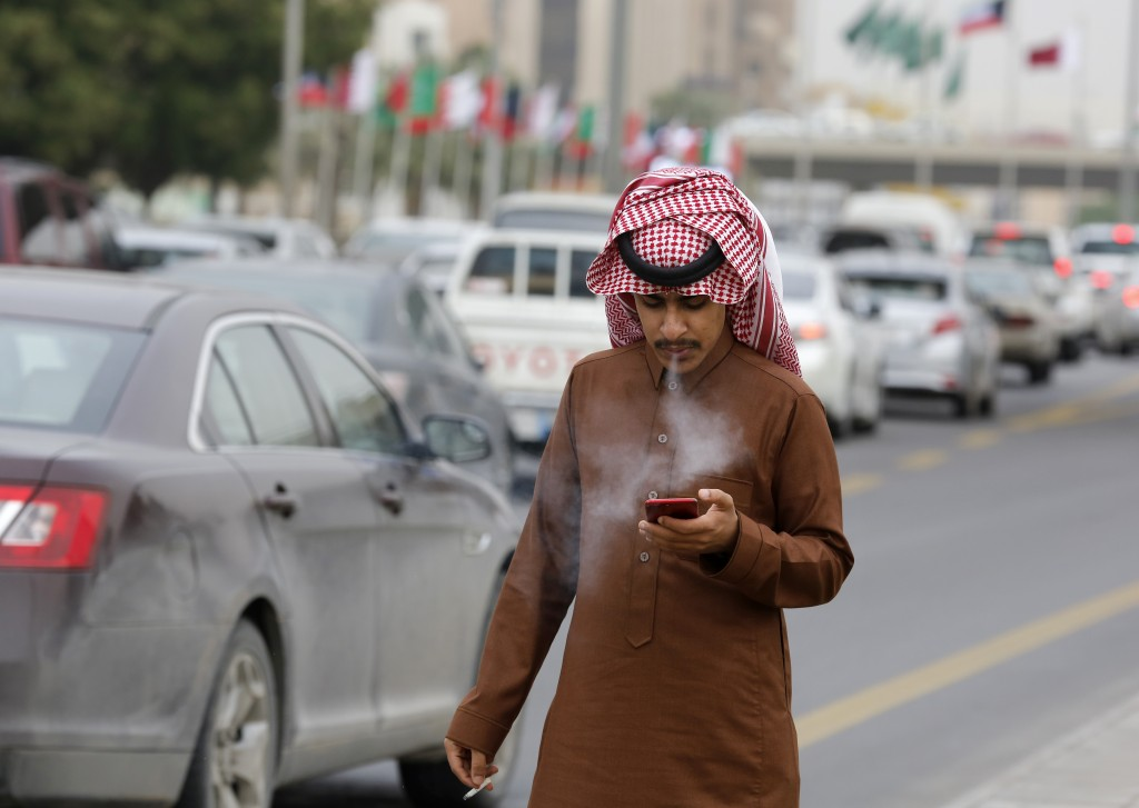 FILE - In this Monday, Dec. 9, 2019 file photo, a man smokes a cigarette as he looks at his mobile phone in Riyadh, Saudi Arabia. On Thursday, Dec. 19...