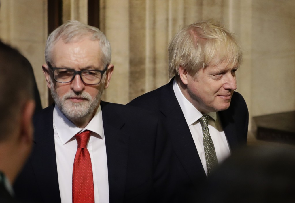 Britain's Prime Minister Boris Johnson, right, and opposition Labour Party Leader Jeremy Corbyn, left, walk through the Commons Members Lobby after he...