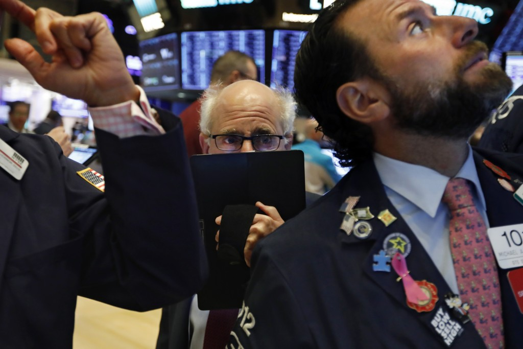 FILE - In this Nov. 4, 2019, file photo trader Peter Tuchman, center, works on the floor of the New York Stock Exchange. Markets are coming off a fabu...