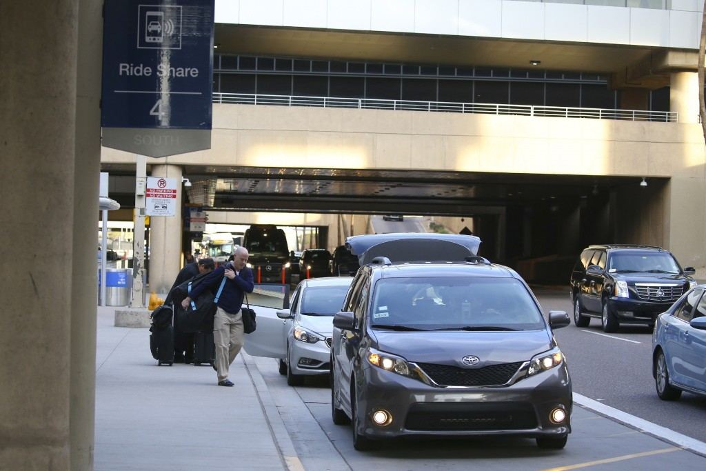 Passengers find their rides at the Ride Share point as they exit Phoenix Sky Harbor International Airport Wednesday, Dec. 18, 2019, in Phoenix. The Ph...