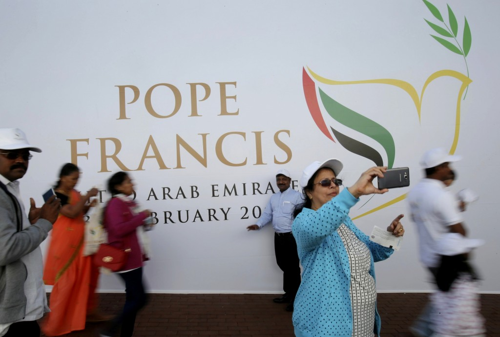 FILE- In this Tuesday, Feb. 5, 2019 file photo, worshippers take selfie in front of a sign on the Pope Francis Mass at the Zayed Sports City in Abu Dh...