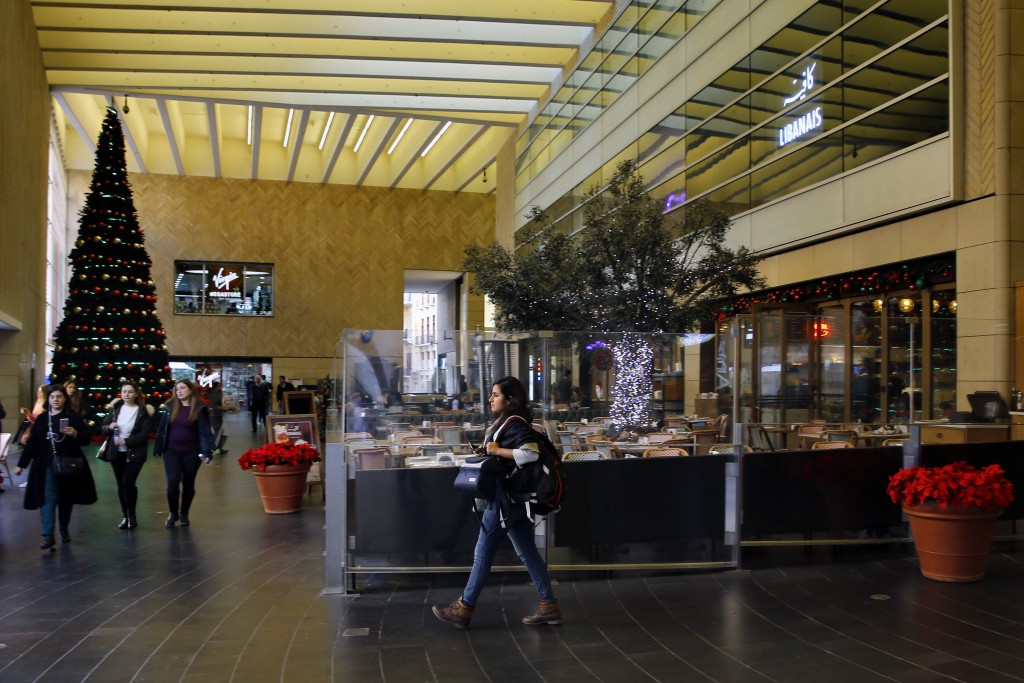 This Wednesday, Dec. 18, 2019 photo, people pass by the almost empty restaurant at the Beirut Souks, in Beirut, Lebanon. Lebanon's unprecedented econo...